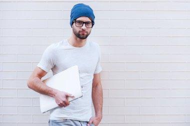 Man in eyeglasses holding laptop