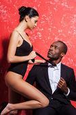 Fotografie Afrikanischer Mann in formeller Kleidung und Frau in Dessous