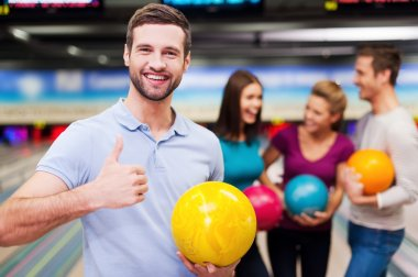 Man holding  bowling ball  and thumb up