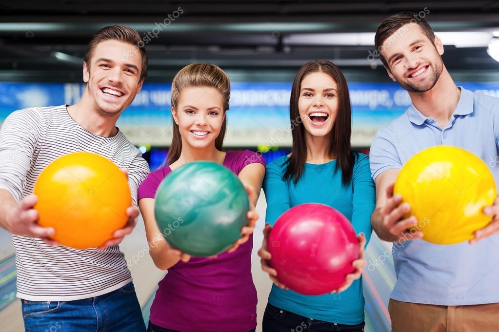 Friends outstretching bowling balls