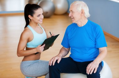 Physical therapist sitting close to senior man