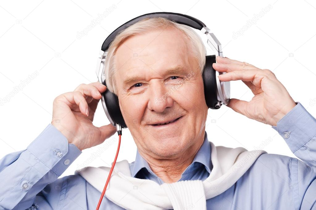senior man in headphones listening to music stock photo
