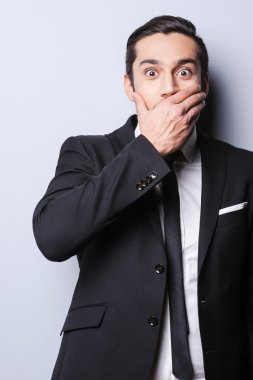 Man in formalwear covering mouth