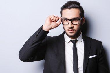 Man in formalwear adjusting his glasses