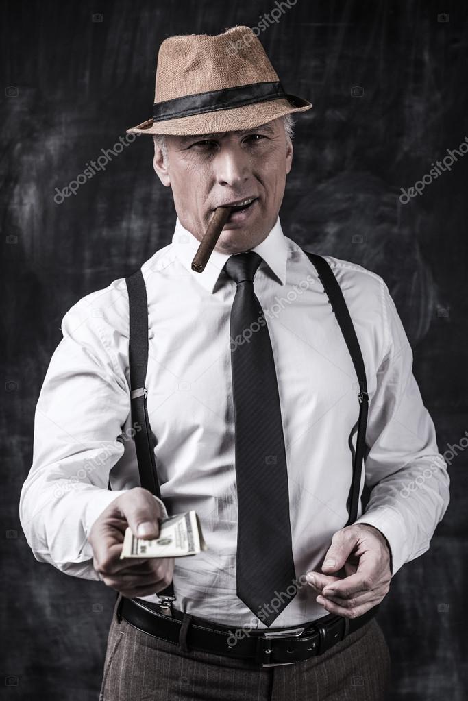 196ldre man i hatt och h228ngslen str228cker ut pengar