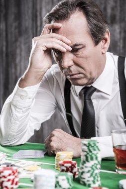 Depressed senior man  sitting at the poker table