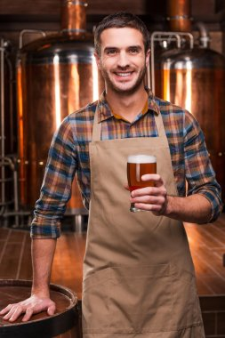 Brewer in apron holding glass with beer