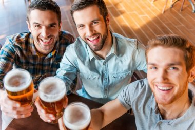Young men  toasting with beer in bar