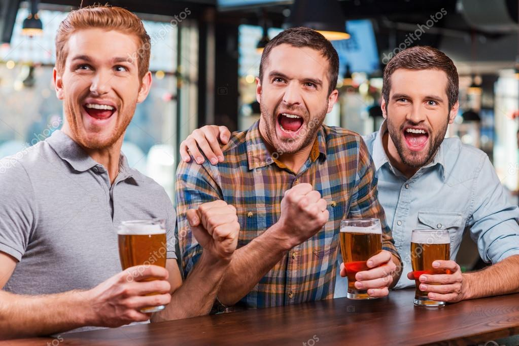 men holding beer and watching football match in bar stock photo men holding beer and watching football match in bar stock photo 61925493