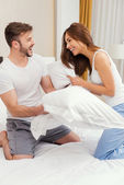 Fotografie Couple fighting with pillows