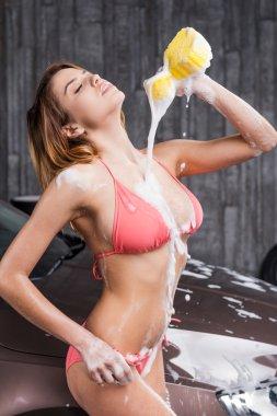 Woman in bikini making body wet