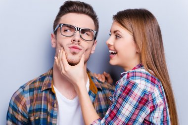 Man grimacing while girlfriend touching his face