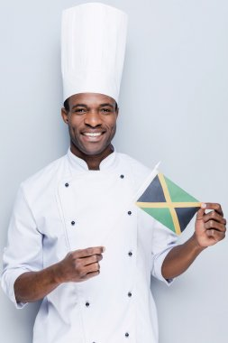 African chef holding flag of Jamaica