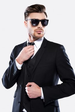 Portrait of handsome young man in formal wear and sunglasses adjusting his necktie and looking at camera stock vector
