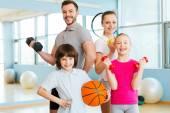 Famiglia che tiene diverse attrezzature sportive