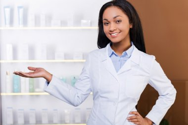 Woman in lab coat in drugstore