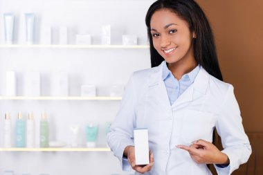 African woman in lab coat holding medicine