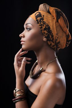 African woman wearing headscarf and touching chin