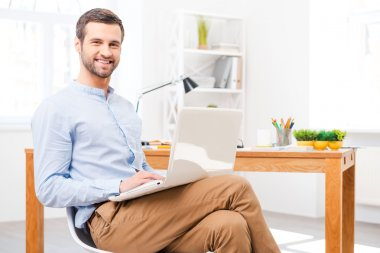 Man in shirt working on laptop in office