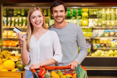 Couple showing credit card in  food store
