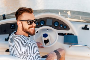 young man driving yacht