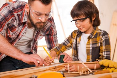 carpenter teaching son to work with wood