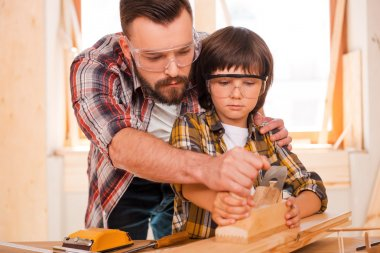 carpenter teaching his son to work with wood