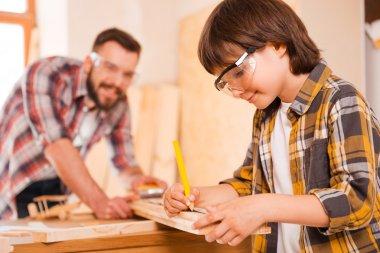 little boy making measurements on wooden plank