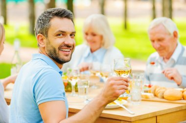 man toasting with wine with family
