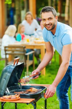 young man barbecuing meat on grill