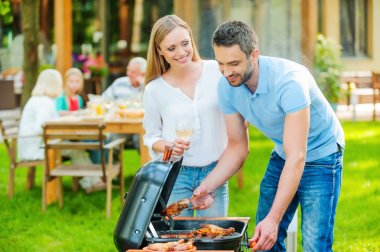couple barbecuing meat on the grill