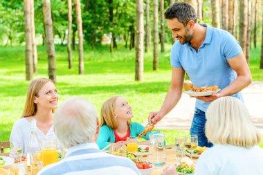 Happy family enjoying mea in garden