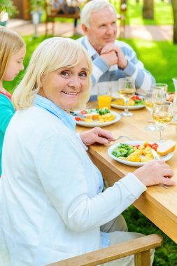 senior woman enjoying dinner with family