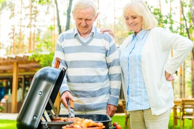 senior couple barbecuing meat on grill