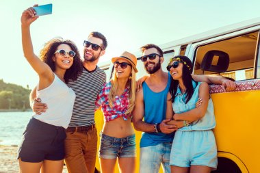 Group of happy young people bonding to each other and making selfie while standing near their retro mini van stock vector