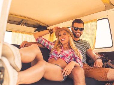 couple sitting at back seats of minivan