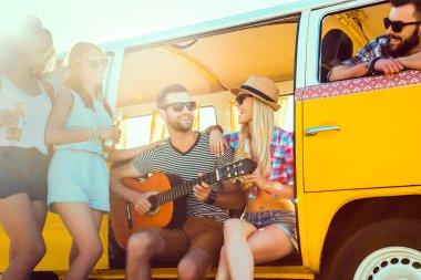 young people enjoying time near minivan