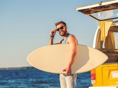 man holding skimboard and adjusting eyewear