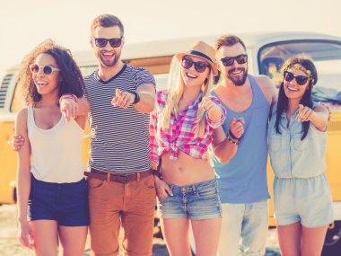 people standing on beach with retro minivan