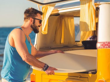 man taking skimboard out of car trunk
