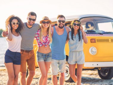 young people embracing and looking at camera while standing on the beach with retro minivan in the background