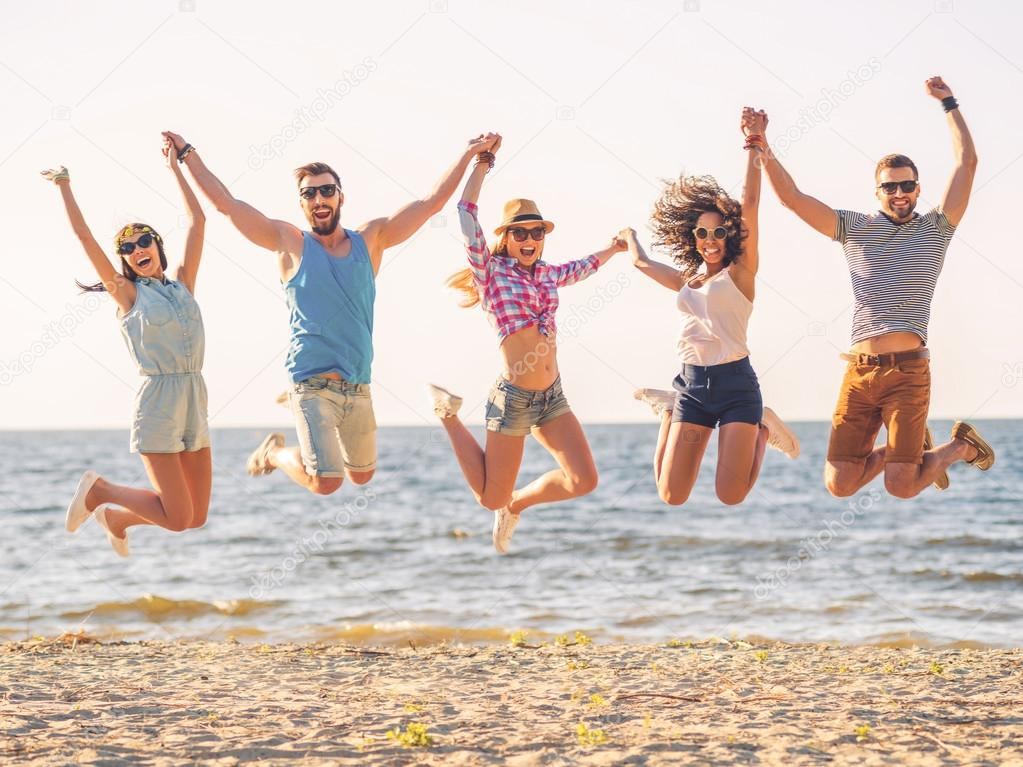 happy young people jumping on beach