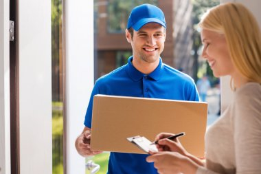 delivery man holding and woman putting signature