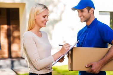 delivery man and woman putting signature in clipboard