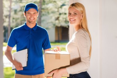 woman holding cardboard box with delivery man