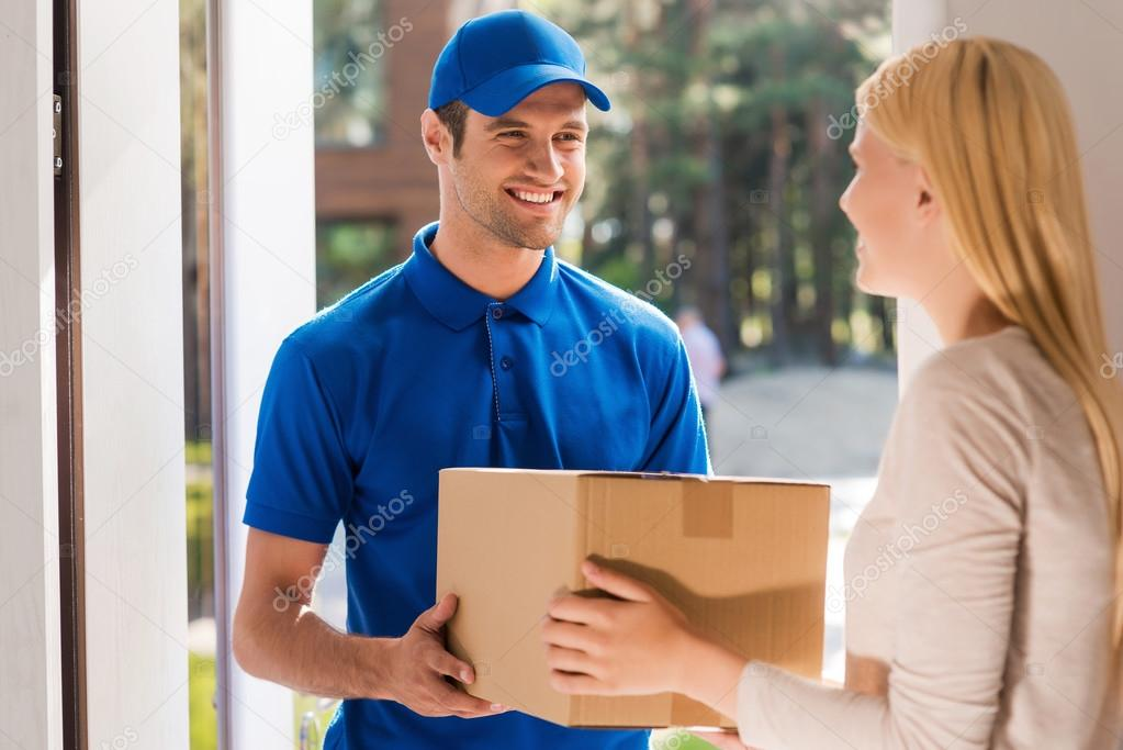 delivery man giving cardboard box to woman stock photo