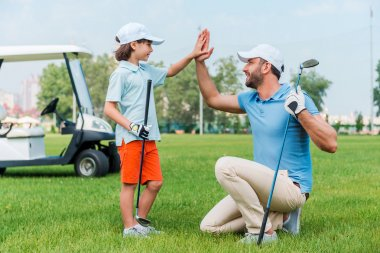 man and son giving high-five on  golf course