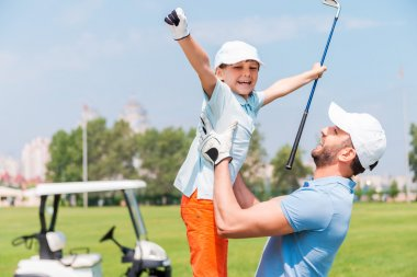 man picking up his son on golf course