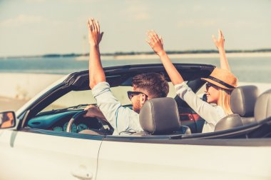 couple keeping arms raised in convertible