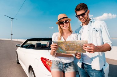 couple examining map near convertible